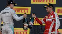 Nico Rosberg a Sebastian Vettel si ťukají šampaňským na pódiu v Suzuce