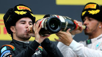 Sergio Pérez a Lewis Hamilton popíjí šampaňské na pódiu v Soči