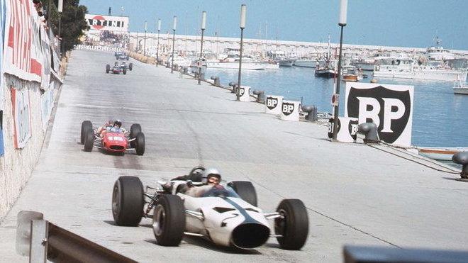 Bruce McLaren v 2. kole Velké ceny Monaka před Lorenzem Bandinim na Ferrari