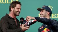 Gerard Butler a Daniel Ricciardo na pódiu po závodě v Austinu