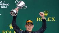 Max Verstappen se raduje z trofeje na pódiu po závodě v Brazílii