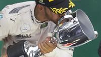Lewis Hamilton se raduje se svou trofejí z vítězství v závodě v Brazílii