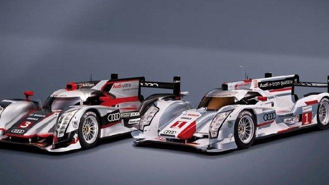 Vozy Audi R18 (v pozadí) a R18 e-tron quattro před Le Mans 2012