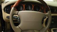 Multifunkční volant je tvořen kůží a dřevem. V pozadí trojice budíků v samostatných kruhových výřezech