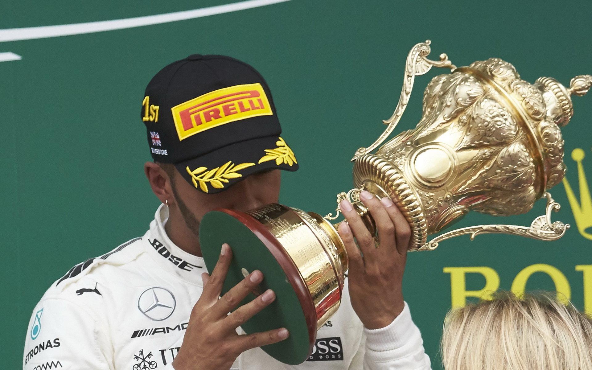 Lewis Hamilton se svou trofejí na pódiu po závodě v Silverstone