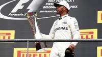 Lewis Hamilton na pódiu se svou trofejí po závodě v Belgii