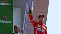 Sebastian Vettel na pódiu se svou trofejí po závodě v Itálii