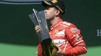 Sebastian Vettel se svou vítěznou trofejí na pódium po závodě v Brazílii