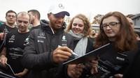 Lewis Hamilton rozdává podpisy zaměstnancům Mercedesu