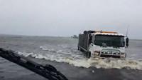 Nákladní vozy brodící se zaplavenou oblastí u města Broome