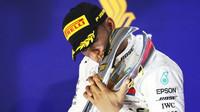 Lewis Hamilton se svou trofejí na pódiu po závodě v Singapuru