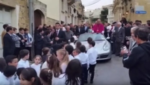 Porsche s arciknězem táhlo 50 dětí, podle místních se jedná o tradici - anotační obrázek
