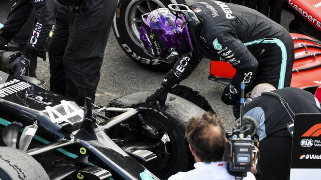 Lewis Hamilton si prohlíží praskloup pneumatiku po závodě v Silverstone