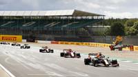 Piloti projíždějí kolem nabouraného vozu Kevina Magnussena v závodě v Silverstone