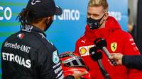 Mick Schumacher předává přilbu svého otce Lewisovi Hamiltonovi na Nürburgringu