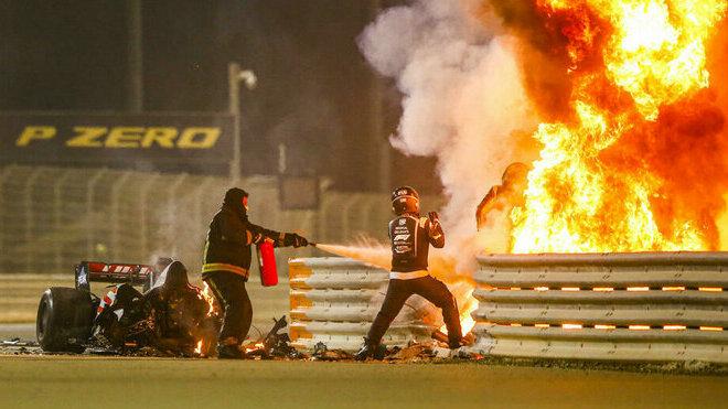 Hořící přední část Grosjeanova vozu za svodidly, jezdec bojuje o život