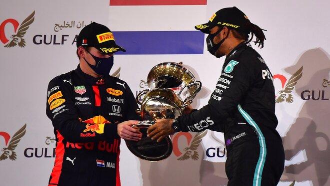 Lewis Hamlton dává potěžkat svou trofej Maxovi Verstappenovi na pódiu v Bahrajnu